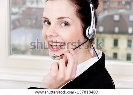 smiling young female callcenter agent with headset in office
