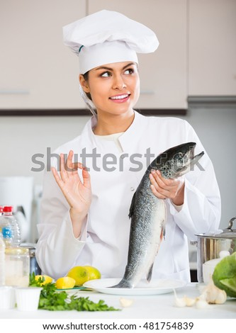Smiling young female chef cooking rainbow trout in commercial kitchen