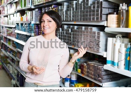 Smiling young female choosing box of hair dye in shop