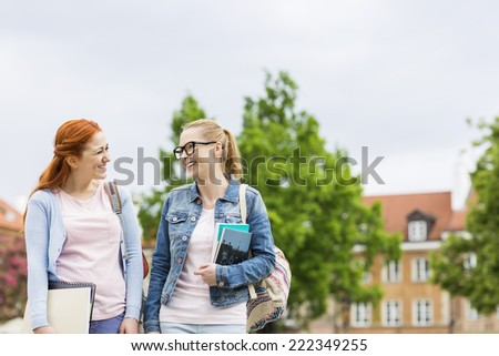 Smiling young female college friends walking outdoors - stock photo