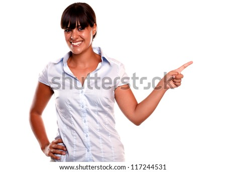 Smiling young female looking at you while pointing left on isolated background - copyspace