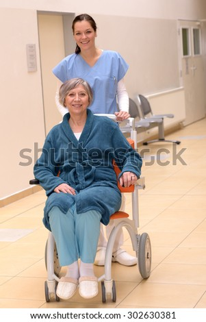 Smiling young female nurse in hospital pushing senior patient in wheelchair in hospital - stock photo