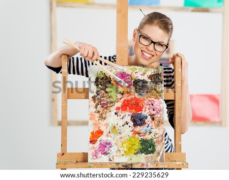Smiling young female painter standing behind wooden easel with colorful oil palette. Portrait of happy girl artist holding brushes.  - stock photo