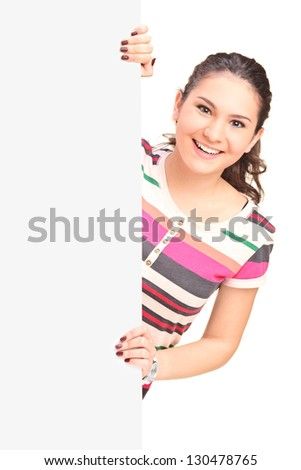 Smiling young female posing on a blank panel isolated on white background