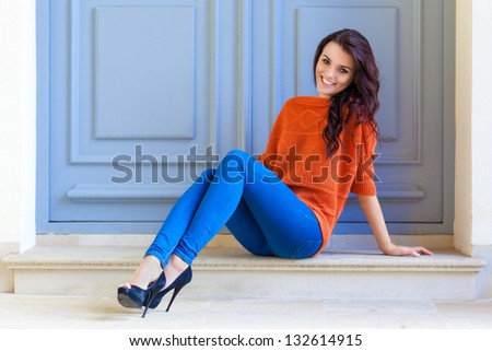 Smiling young female sitting at front door - stock photo