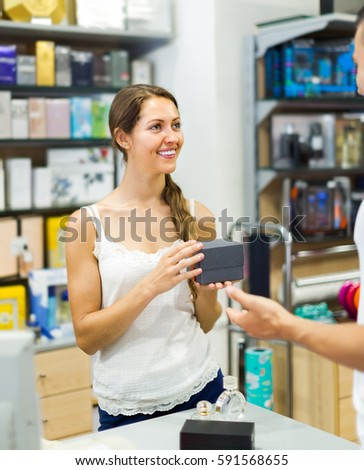 Smiling young female store clerk serving purchaser at cash desk