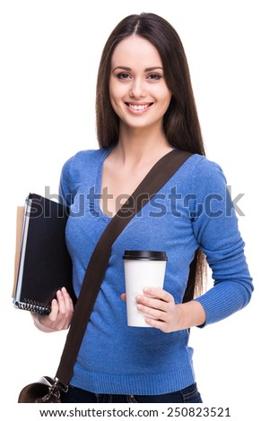 Smiling young female student with books and a cup of coffee, isolated on white background. - stock photo