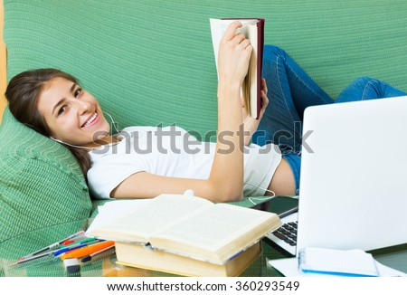 Smiling young female student with earphones doing homework lying on sofa at home - stock photo