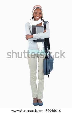 Smiling young female student with her books against a white background