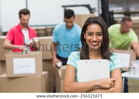 Smiling young female volunteer holding clipboard in a large warehouse - stock photo