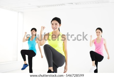 smiling young fit group stretching in gym