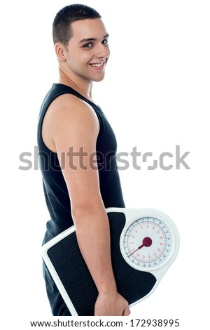 Smiling young fitness trainer holding weighing scale