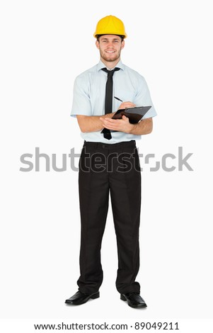 Smiling young foreman taking notes on his clipboard against a white background - stock photo