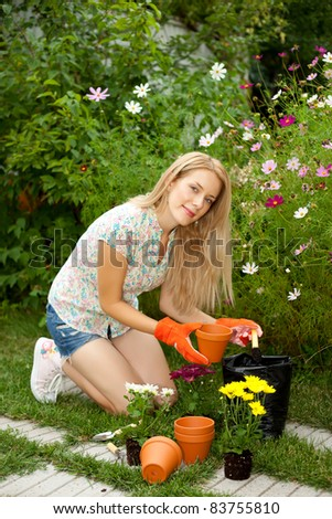Smiling young gardener with gloves planting flowers - stock photo