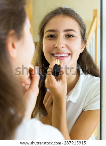 Smiling young girl admiring himself in front of the mirror - stock photo