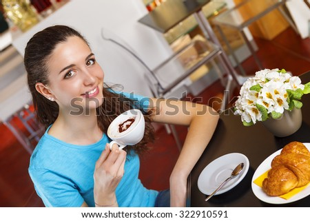 Smiling Young girl at the bar having a coffee break with heart shaped cappuccino - stock photo