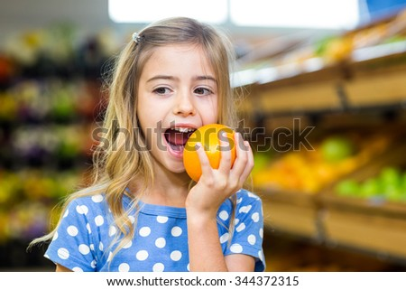 Smiling young girl eating an orange at supermarket - stock photo