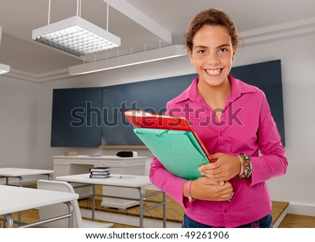 Smiling young girl holding a pair of files in a classroom