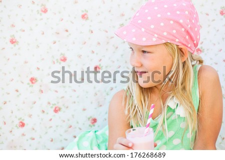 Smiling young girl holding milk fruit smoothie in glass with striped straw - stock photo