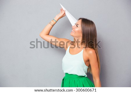 Smiling young girl holding paper plane over gray background - stock photo