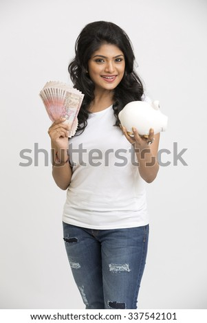 Smiling young girl holding rupee notes and piggy bank in her hands on white background. - stock photo