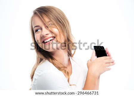 Smiling young girl holding smartphone isolated on a white background. Looking away