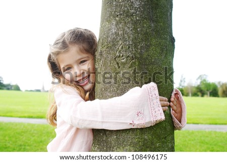 Smiling young girl hugging a tree in the park. - stock photo