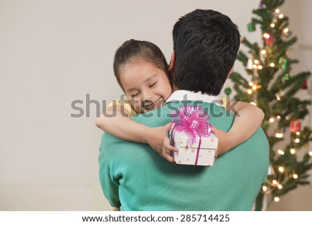 Smiling young girl hugging her dad while holding gift - stock photo