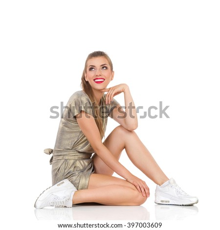 Smiling young girl in gold mini dress and white sneakers sitting on floor and looking up. Side view. Full length studio shot isolated on white.