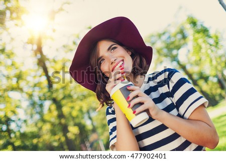 smiling young girl in park holding drink, sunny rural landscape