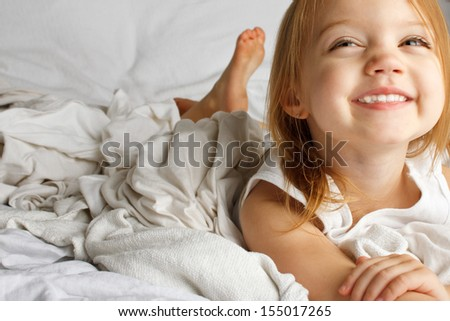 Smiling young girl in white covered bed - stock photo