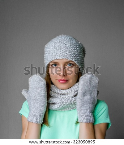 Smiling young girl in winter cap, scarf and mittens