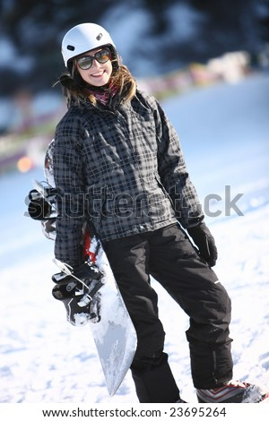 Smiling young girl keeping snowboard - stock photo