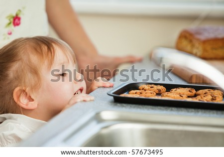 Smiling young girl looking at cookie in the kitchen - stock photo