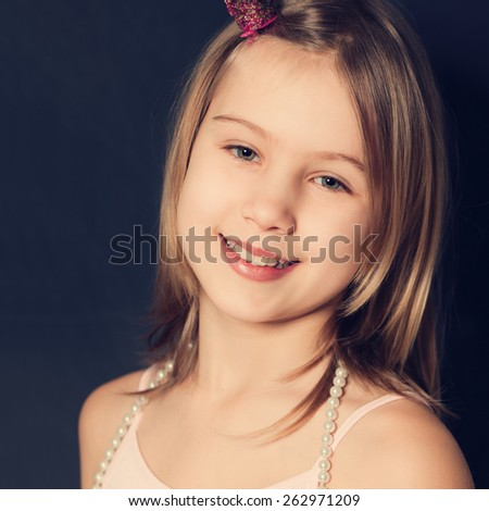 Smiling young girl on dark background, cute face closeup - stock photo