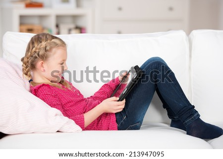 smiling young girl reading on tablet-pc at home - stock photo