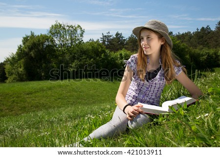Smiling Young Girl Resting In A Beautiful Field Of Grass Enjoying A beautiful Sunny Spring Day In Beautiful Nature - stock photo
