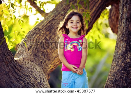 Smiling young girl standing on tree branches with green leaves