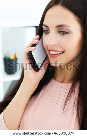 Smiling young girl talking on the mobile phone sitting at office. Advertisement concept.