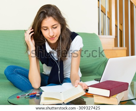 Smiling young girl using laptop on sofa at home  - stock photo