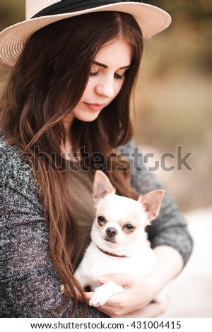 Smiling young girl wearing hat holding chihuahua outdoors. Woman with pet dog.