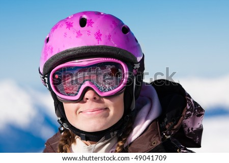 Smiling young girl wearing ski mask and helmet. Winter sport vacation - stock photo