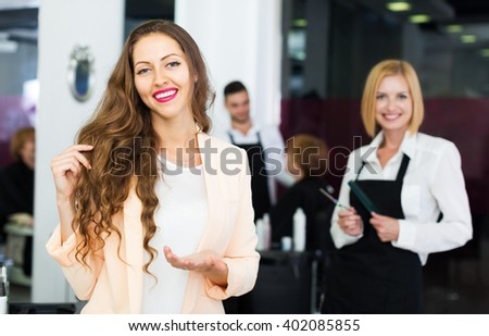 Smiling young girl with the hairstylist in the beauty salon - stock photo
