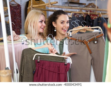 Smiling young girls choosing new clothes in shop