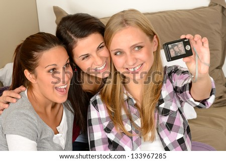 Smiling young girls taking self portrait at home