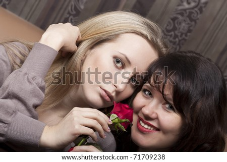Smiling young girls with a flower - stock photo