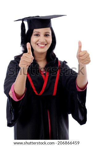 Smiling young graduation student making thumbs up gesture against white