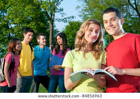 Smiling young group of students studying together outdoor at the college park - stock photo