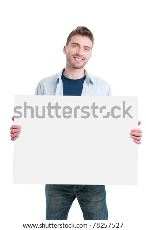 Smiling young guy holding white poster to write it on your own text