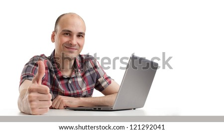 Smiling young guy using laptop computer and showing his thumb up - stock photo